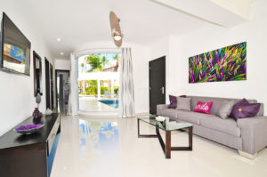 living room with large window with pool view in ground floor condo at The SANCTUARY at Los Corales