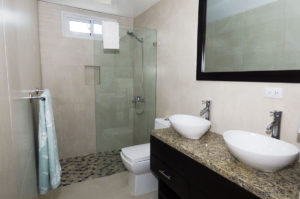 bathroom with double sinks and standing shower in penthouse condo at The SANCTUARY at Los Corales
