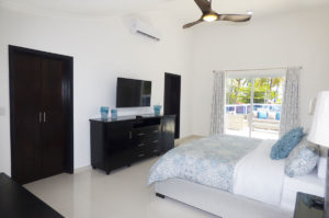 bedroom with TV, dresser, and balcony in penthouse condo at The SANCTUARY at Los Corales
