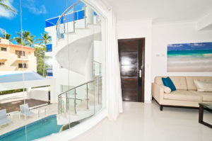 living room with view of large window showing the pool and spiral staircase at second floor condo at The SANCTUARY at Los Corales