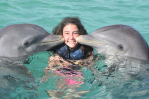 Happy young girl laughing and swimming with dolphins in the blue swimming pool on a bright sunny day