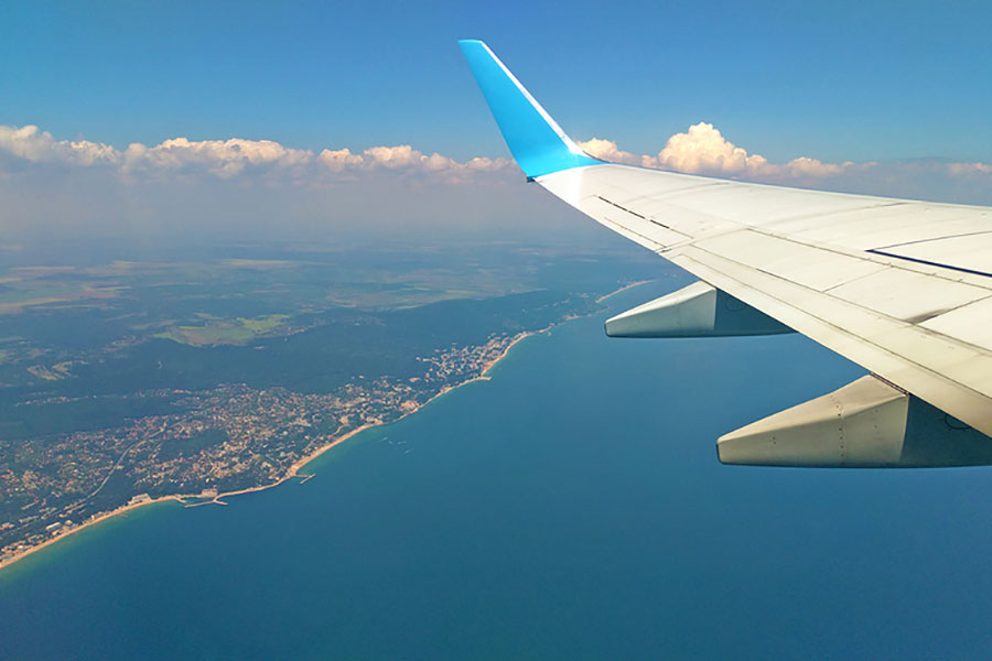 Airplane wing view out of the window on the cloudy sky The Earth and the blue sea background