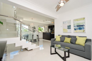penthouse condo living room with view of staircase and kitchen at The SANCTUARY at Los Corales