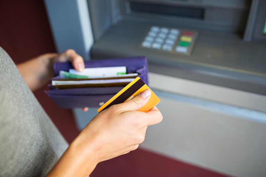 close up of hands with cash and credit card at atm machine